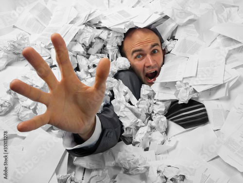 Photo  Businessman sinking in heap of documents
