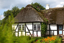 Danish Farmhouse With Thatched Roof And Blooming Garden