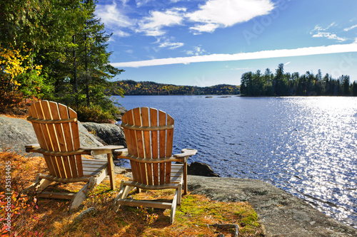 Adirondack chairs at lake shore Wallpaper Mural