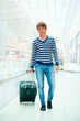 Portrait of young man walking inside modern airport with trolley