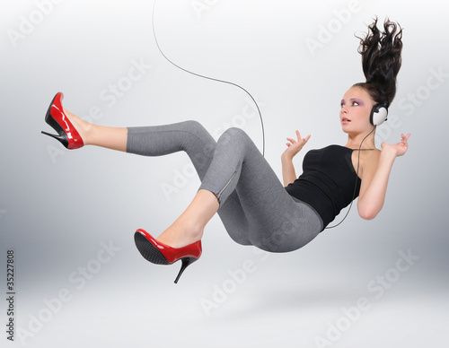 Obraz na plátne Young girl with headphones in unreal pose