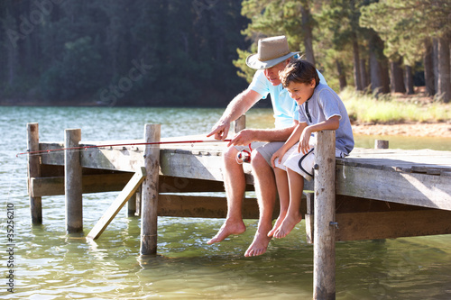Senior man fishing with grandson Canvas-taulu