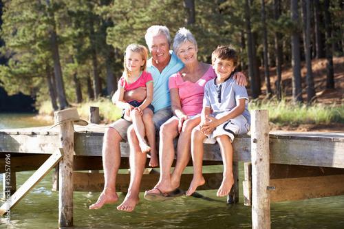 Valokuvatapetti Senior couple sitting by lake with grandchildren