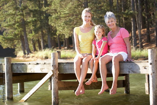 Mother,daughter and grandmother sitting by lake Canvas-taulu
