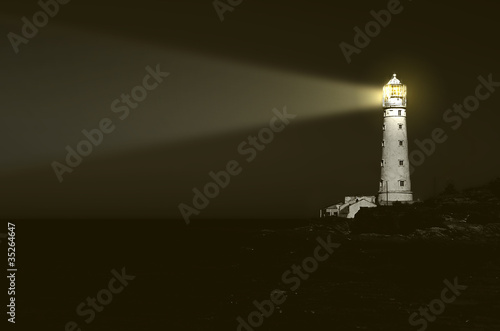 Foto op Aluminium Vuurtoren lighthouse at night: beam of light over sea