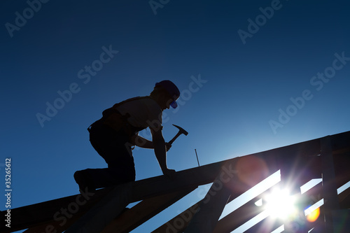 Fotografiet Builder or carpenter working on the roof