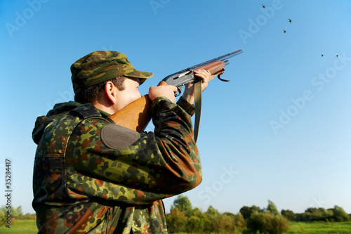 Fotografie, Obraz  hunter shooting with rifle gun