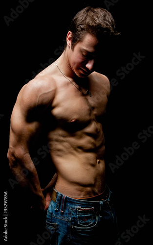 Muscle sexy naked young man posing in the dark Tablou Canvas