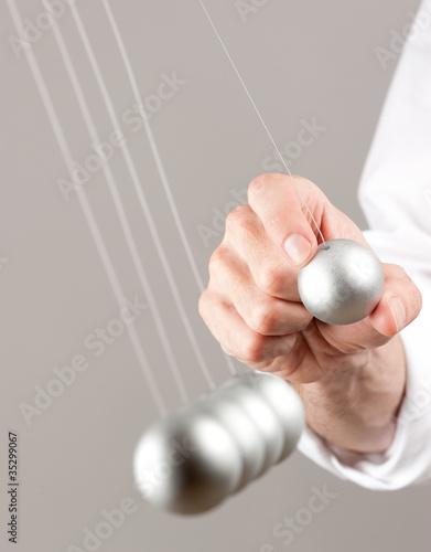 Fotografie, Obraz  hand with newton pendulum