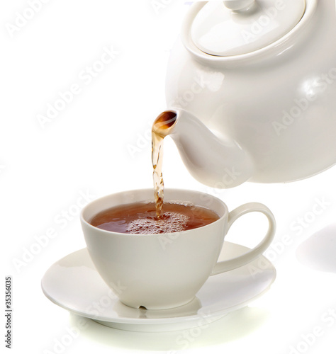 Staande foto Thee Tea being poured into tea cup isolated on a white background