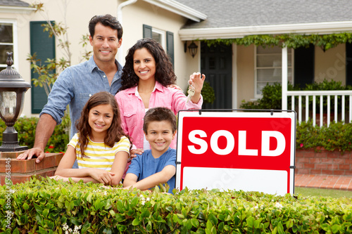 Valokuvatapetti Hispanic family outside home with sold sign