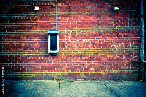 Deurstickers Graffiti Obsolete Payphone on a Grungy Urban Brick Wall