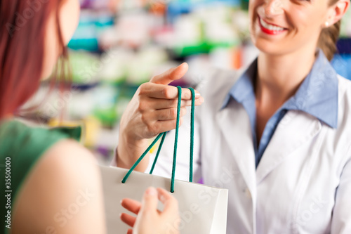 Fotobehang Apotheek Female pharmacist in her pharmacy with a client