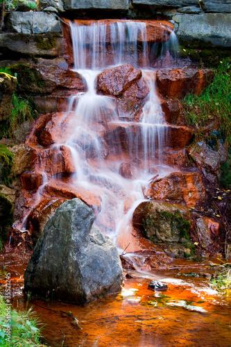wodospad-kaskadowe-ponad-czerwone-skaly-pokryte-algami