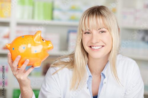 Fototapeta lächelnde apothekerin hält  sparschwein in der hand obraz