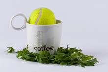 A Tennis Ball In A Cup Of Coff...