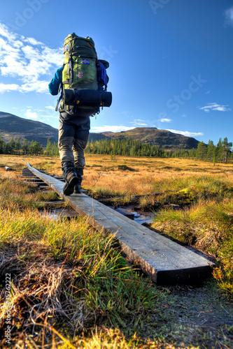 Foto  Wanderer mit Rucksack auf dem Weg durch Moorlandschaft