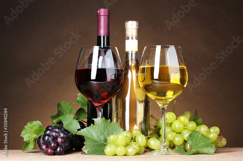 Fototapety, obrazy: Glasses of wine, bottles and grapes on yellow background