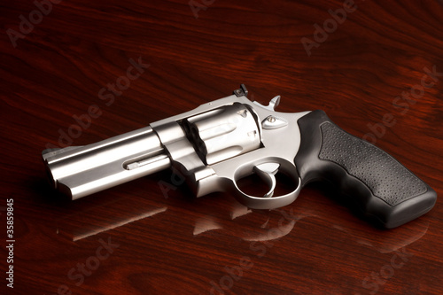 Fotografia, Obraz  Clean .357 revolver laying on reflective wooden table