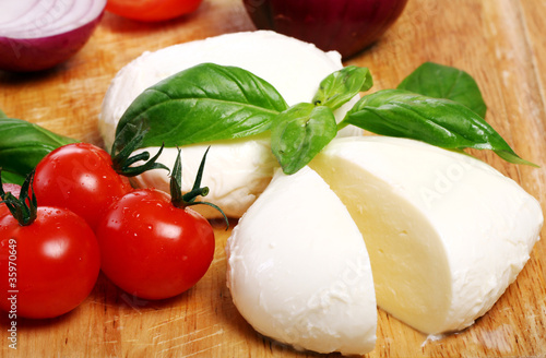Poster Dairy products Tomatoes, basil and mozzarella on wooden board