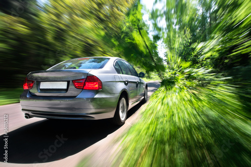 Car moving fast on forest road