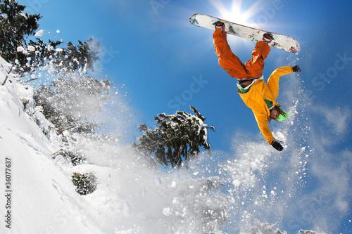 Fotografie, Obraz  Snowboarder jumping against blue sky