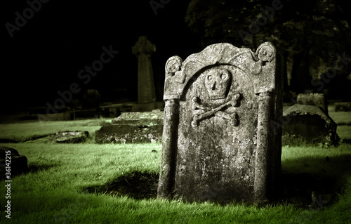 Gravestone with skull and bones in old cemetery, dramatic light Fototapete