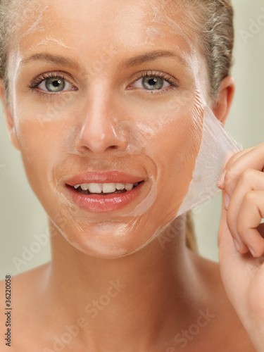 Fotografie, Tablou  young woman peeling off a facial mask