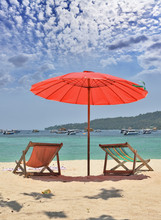 Red Beach Umbrella And Deck Chairs