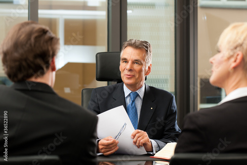 Photo Lawyer or notary with clients in his office