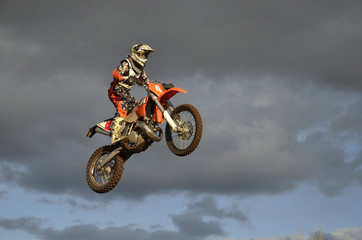 Fototapeta The spectacular jump motocross racer on a motorcycle