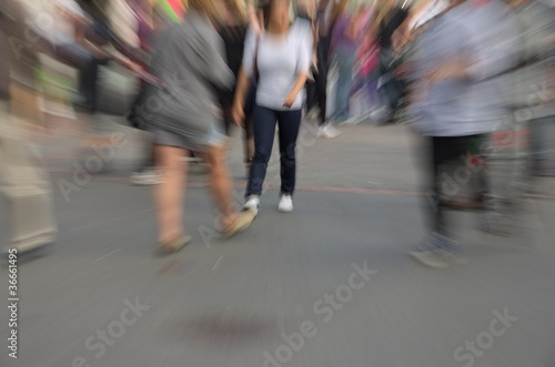 Motion and zoom blurry people walking on city street Canvas Print