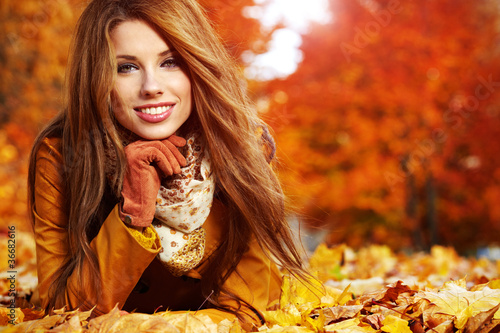 Portrait of an autumn woman lying over leaves and smiling - 36682616