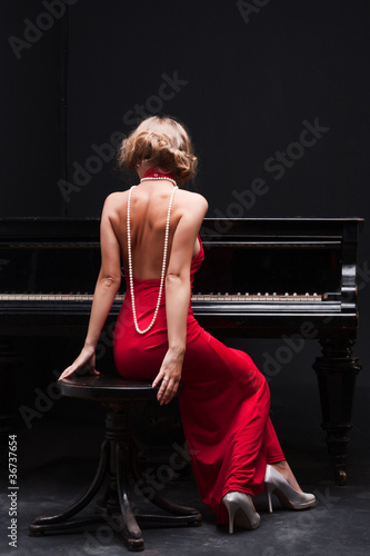 Wall Murals Bestsellers beautiful young attractive woman in cocktail dress and piano