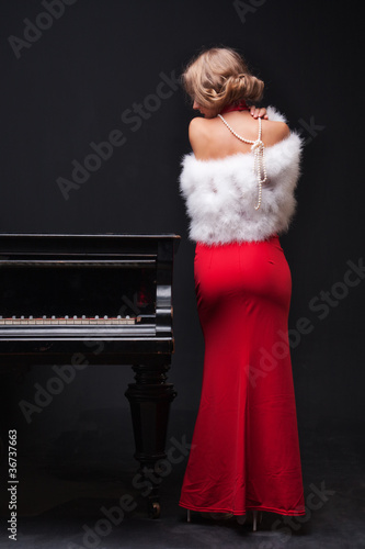 Papiers peints Rouge, noir, blanc beautiful young attractive woman in evening dress and piano