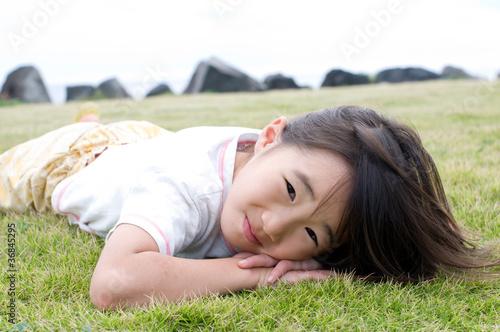 Fotografie, Obraz  芝生で寝転ぶ女の子