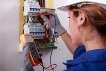Female Electrician Taking Reading From Fuse Box