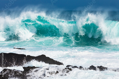 Foto-Leinwand - Turquoise rolling wave slaming on the rocks (von pwollinga)