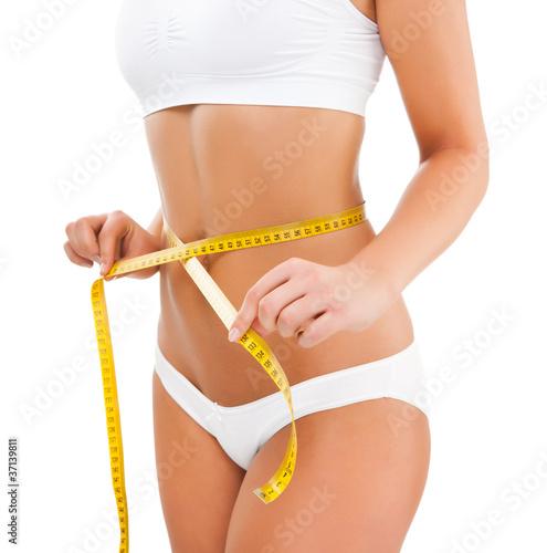 Obraz Woman measuring her slim body isolated on white - fototapety do salonu
