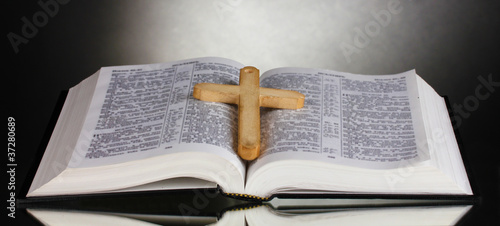 Russian open holy bible with wooden cross on black backround