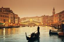 Rialto Bridge And Gondolas At A Foggy Autumn Evening In Venice.