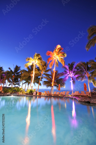 Foto op Plexiglas Feeën en elfen Swimming pool with palm trees at night time