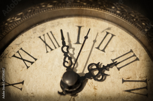 Antique clock on grunge background