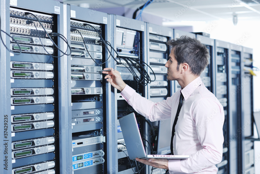 Fototapeta businessman with laptop in network server room