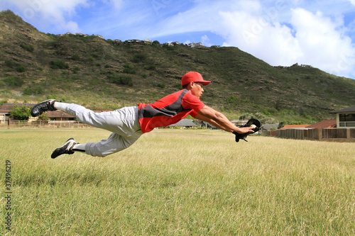 Photo  Baseball player dives to catch the ball