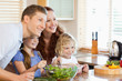 Family together with salad in the kitchen