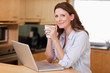 Woman drinking coffee while on laptop