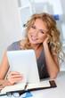 Beautiful woman in office using digital tablet