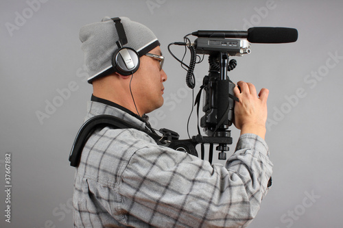 Fotografie, Obraz  Man with HD SLR camera and audio equipment