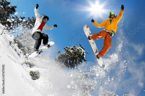 Poster Glisse hiver Snowboarders jumping against blue sky